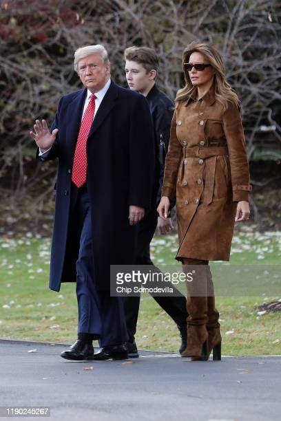 S President Donald Trump first lady Melania Trump and their son Barron Trump walk across the South Lawn before leaving the White House on board...