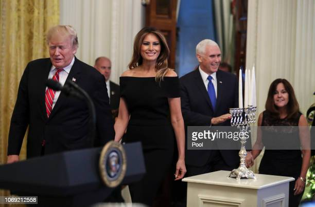 President Donald Trump first lady Melania Trump Vice President Mike Pence and his wife Karen Pence attend a Hanukkah reception in the East Room of...