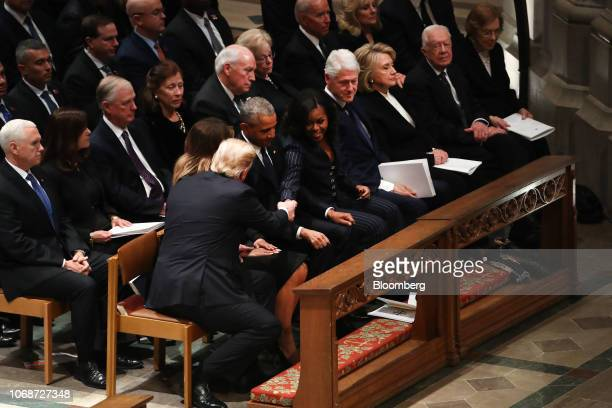 US President Donald Trump first row left shakes hands with former US First Lady Michelle Obama center while US First Lady Melania Trump from top row...