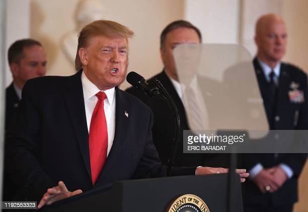 President Donald Trump, flanked by advisors, reads from the teleprompter as he addresses the situation with Iran in the Grand Foyer of the White...