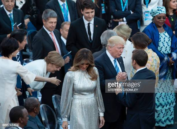 TOPSHOT President Donald Trump flanked by First Lady Melania Trump greets French President Emmanuel Macron before a concert by La Scala Philharmonic...
