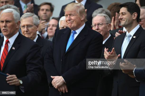 S President Donald Trump flanked by Republican lawmakers celebrates Congress passing the Tax Cuts and Jobs Act on the South Lawn of the White House...