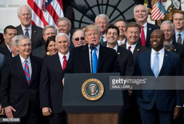 US President Donald Trump flanked by Republican lawmakers speaks about the passage of tax reform legislation on the South Lawn of the White House in...