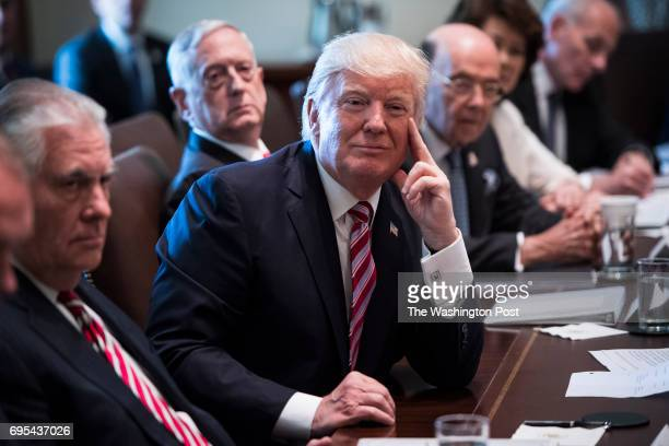 President Donald Trump flanked by Secretary of State Rex Tillerson left and Defense Secretary Jim Mattis center left listens during a Cabinet meeting...