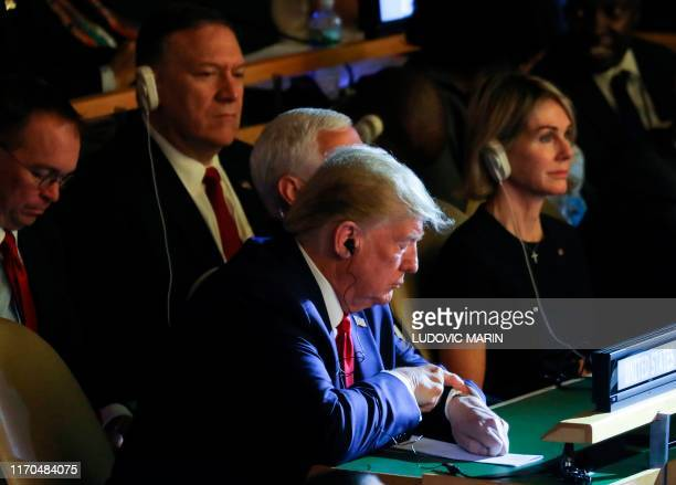 President Donald Trump flanked by US Vice President Mike Pence US Secretary of State Mike Pompeo and US ambassador to the UN Kelly Craft checks his...