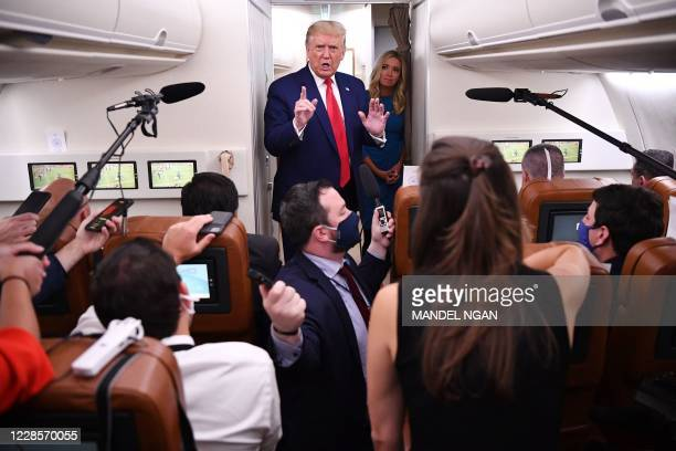 President Donald Trump, flanked by White House Press Secretary Kayleigh McEnany, speaks to reporters onboard Air Force One after a campaign rally in...