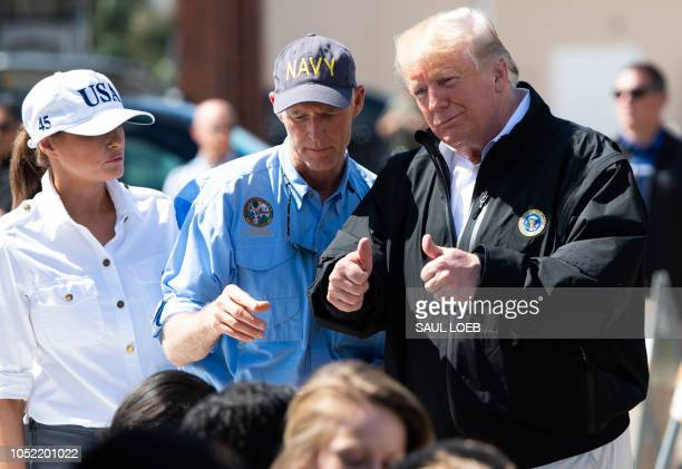 US President Donald Trump Florida Governor Rick Scott and First Lady Melania Trump hand out bottles of water as they tour damage from Hurricane...