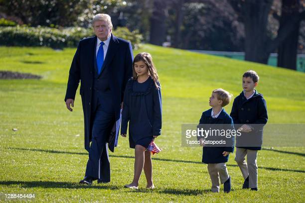 President Donald Trump, followed by his grandchildren, Arabella Kushner, Theodore Kushner, and Joseph Kushner walk on the south lawn of the White...