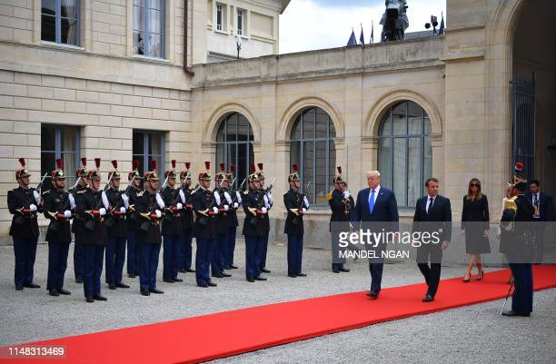 US President Donald Trump French President Emmanuel Macron and US First Lady Melania Trump walk past Republican Guards as they arrive for a meeting...