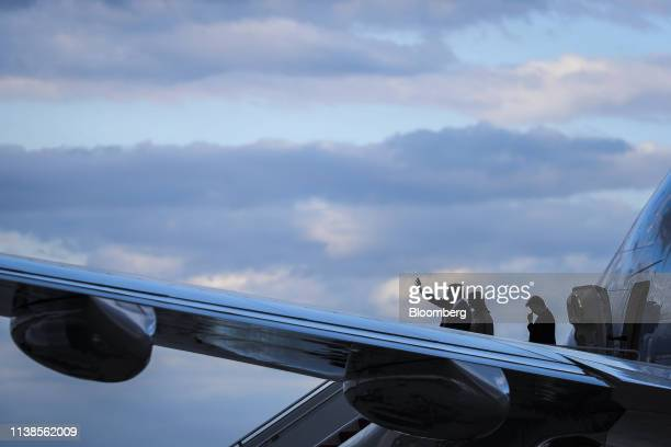 US President Donald Trump from left waves as he walks with US First Lady Melania Trump and son Barron Trump as he arrives aboard Air Force One in...