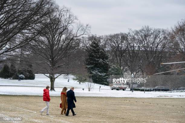 US President Donald Trump from right First Lady Melania Trump and son Barron Trump walk towards Marine One on the South Lawn of the White House in...