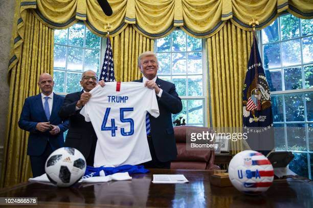 US President Donald Trump from right is presented a game jersey by Carlos Cordeiro president of the United States Soccer Federation as Gianni...