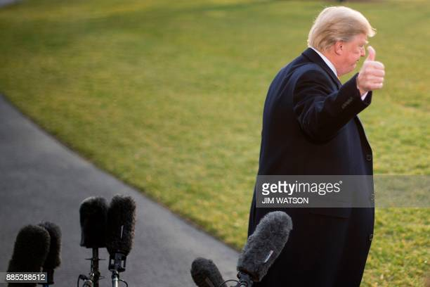 President Donald Trump gestures after making a statement to the press upon his departure at the White House in Washington DC on December 4 2017 / AFP...