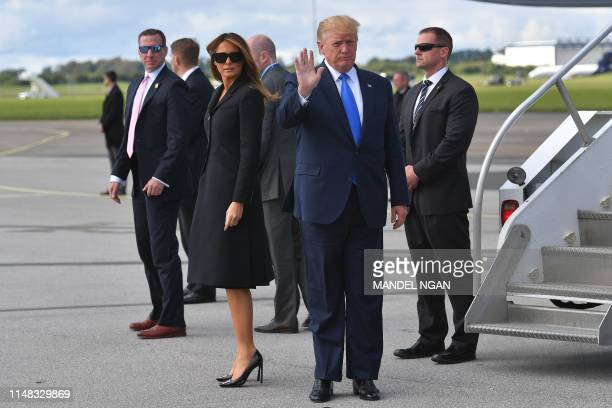 US President Donald Trump gestures as First Lady Melania Trump looks on after disembarking Air Force One upon arrival at Shannon Airport in Shannon...