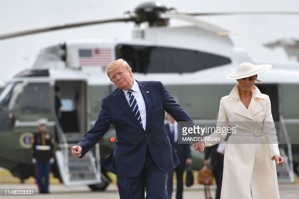 US President Donald Trump gestures as he and First Lady Melania Trump walk off of Marine One to board Air Force One before departing from Southampton...