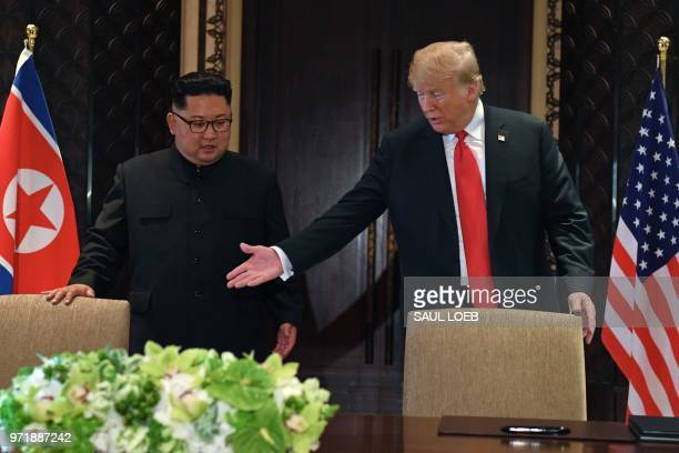 US President Donald Trump gestures as he and North Korea's leader Kim Jong Un arrive for a signing ceremony during their historic USNorth Korea...