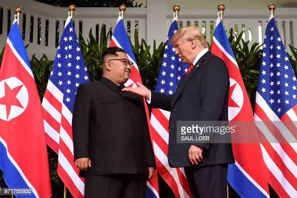 President Donald Trump gestures as he meets with North Korea's leader Kim Jong Un at the start of their historic USNorth Korea summit at the Capella...