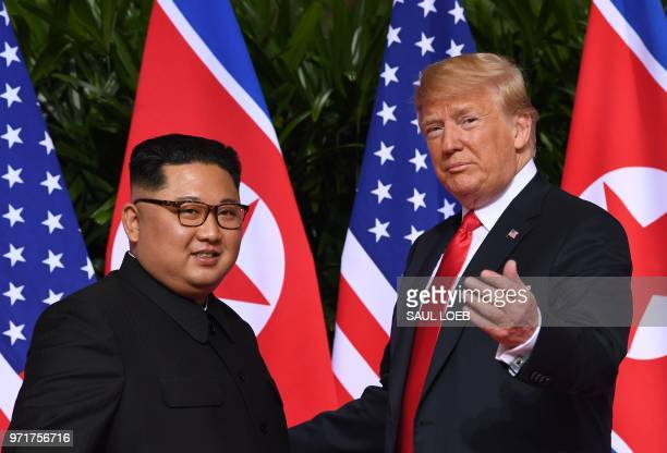 US President Donald Trump gestures as he meets with North Korea's leader Kim Jong Un at the start of their historic USNorth Korea summit at the...