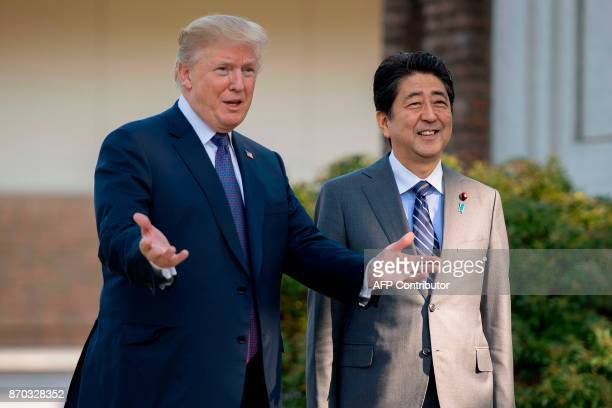US President Donald Trump gestures as he speaks with Japan's Prime Minister Shinzo Abe upon arrival for a luncheon at the Kasumigaseki Country Club...