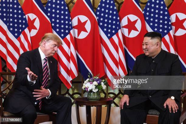 US President Donald Trump gestures as he speaks with North Korea's leader Kim Jong Un during a meeting at the Sofitel Legend Metropole hotel in Hanoi...