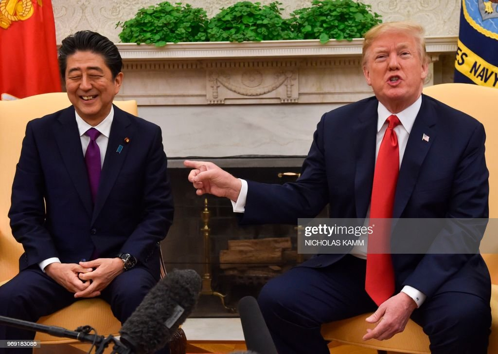 President Donald Trump gestures as Japan's Prime Minister Shinzo Abe smiles in the Oval Office at the White House on June 7, 2018 in Washington, DC.