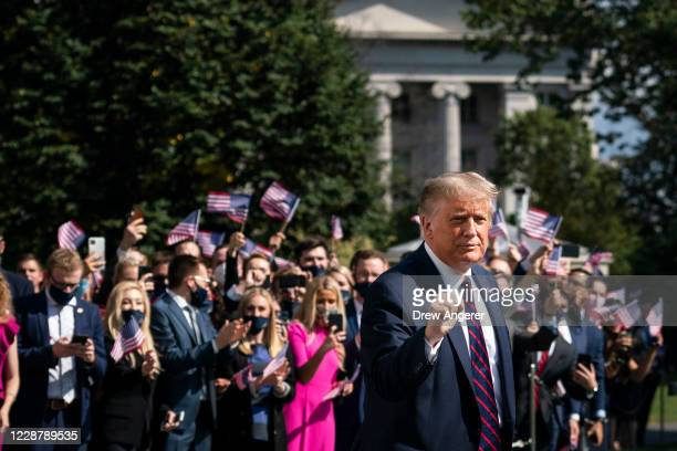 President Donald Trump gestures as White House interns cheer him on as he leaves the White House residence for Marine One on the South Lawn of the...