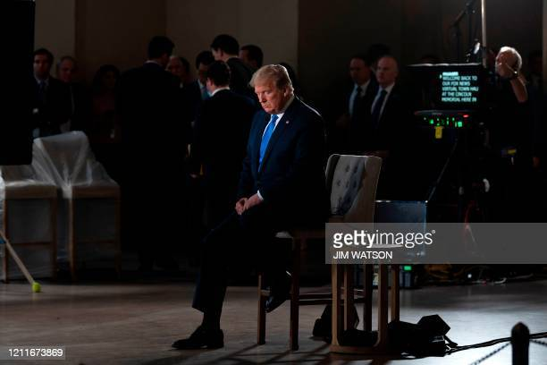"""President Donald Trump gestures during a commercial break of a Fox News virtual town hall """"America Together: Returning to Work,"""" event from the..."""