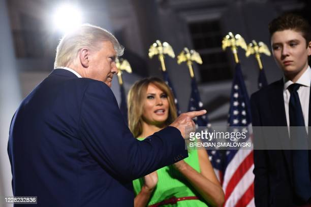 President Donald Trump gestures, flanked by First Lady Melania Trump and son Barron Trump, as they prepare to leave after he delivered his acceptance...