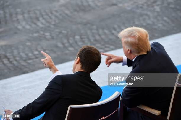 US President Donald Trump gestures next to French President Emmanuel Macron during the annual Bastille Day military parade on the ChampsElysees...