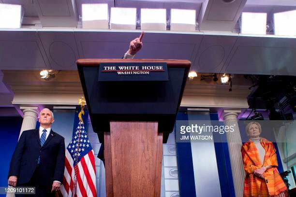 President Donald Trump gestures over the lectern as he speaks, flanked by Health and Human Services Secretary Alex Azar, US Vice President Mike Pence...
