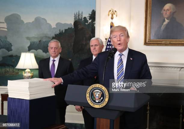 S President Donald Trump gestures to the $13 trillion spending bill passed by Congress early Friday with Vice President Mike Pence and Defense...