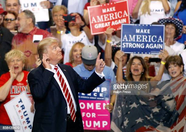 S President Donald Trump gestures to the crowd of supporters at the Phoenix Convention Center as he takes the stage during a rally on August 22 2017...