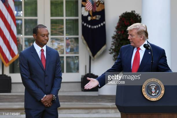 US President Donald Trump gestures to US golfer Tiger Woods during an event to present him with the Presidential Medal of Freedom in the Rose Garden...