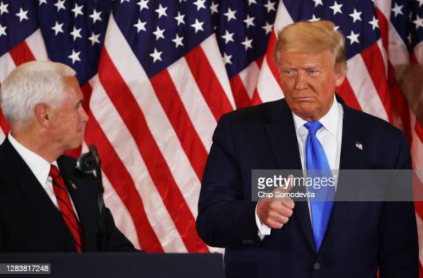 President Donald Trump gestures to Vice President Mike Pence on election night in the East Room of the White House in the early morning hours of...