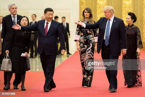 President Donald Trump gestures toward China's President Xi Jinping as US First Lady Melania Trump and Xi's wife Peng Liyuan look on the Great Hall...