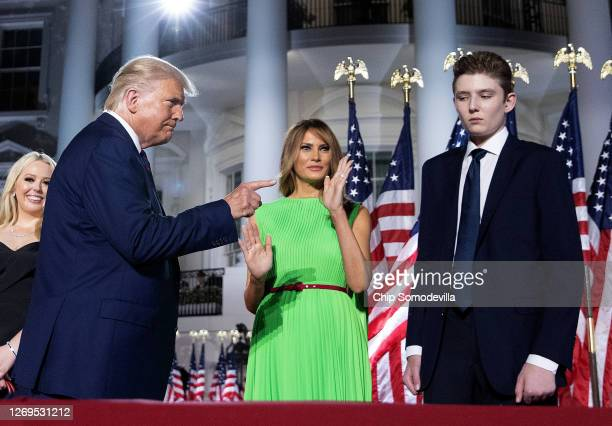 President Donald Trump gestures toward first lady Melania Trump and his son Barron Trump after delivering his acceptance speech for the Republican...