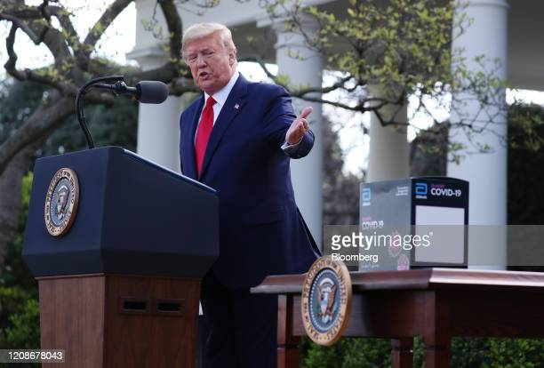 President Donald Trump gestures towards a Abbott Laboratories ID Now Covid-19 test kit during a Coronavirus Task Force news conference in the Rose...