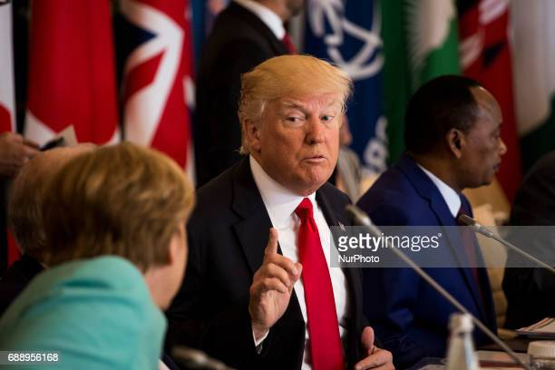 US President Donald Trump gestures towards German Chancellor Angela Merkel during the G7 Summit expanded session in Taormina Sicily on May 27 2017