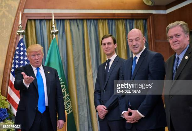 US President Donald Trump gestures watched by senior advisor Jared Kushner Director of the National Economic Council Gary Cohen and Chief Strategist...