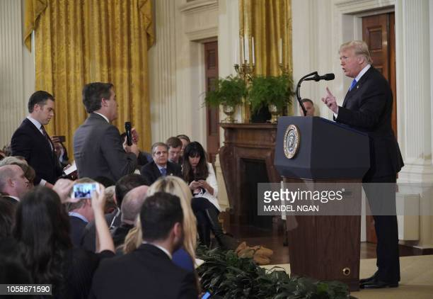 US President Donald Trump gets into a heated exchange with CNN chief White House correspondent Jim Acosta as NBC correspondent Peter Alexander looks...