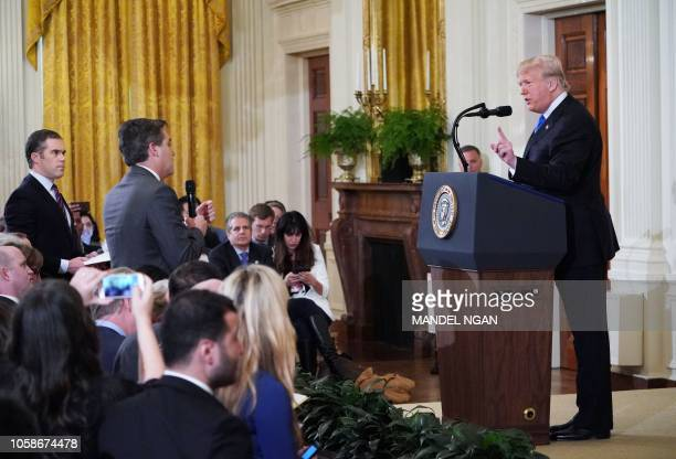 President Donald Trump gets into a heated exchange with CNN chief White House correspondent Jim Acosta as NBC correspondent Peter Alexander looks on...