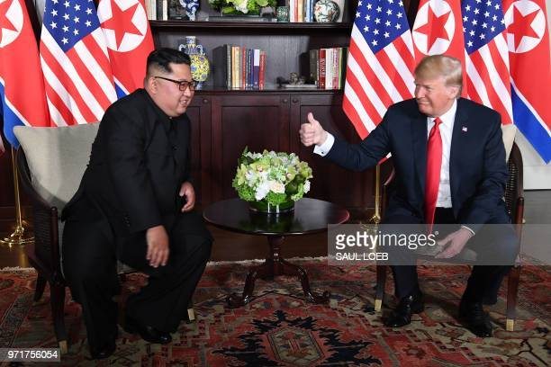 President Donald Trump gives a thumbs up as he sits down with North Korea's leader Kim Jong Un for their historic USNorth Korea summit at the Capella...