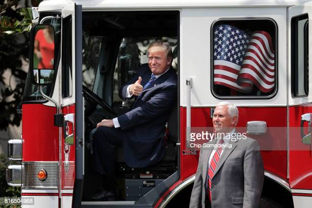 S President Donald Trump gives a thumbs up to journalists from inside a fire engine made by Pierce Manufacturing while touring a Made in America...