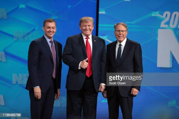 S President Donald Trump gives a thumbs up to the crowd as he stands on stage along with NRA Executive Vice President Wayne LaPierre and Executive...
