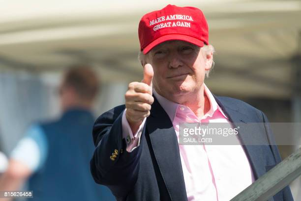 US President Donald Trump gives a thumbsup well wishers as he arrives at the 72nd US Women's Open Golf Championship at Trump National Golf Course in...