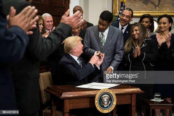 President Donald Trump gives Isaac Newton Farris Jr the pen he used to sign a proclamation to honor Martin Luther King Jr day in the Roosevelt Room...