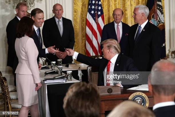 S President Donald Trump gives the signing pen to NASA Administrator Jim Bridenstine after he signed an executive order during a meeting of the...