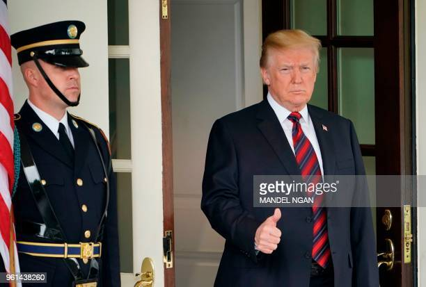 President Donald Trump gives the thumbs-up as he awaits the arrival of South Korea's President Moon Jae-in outside of the West Wing of the White...