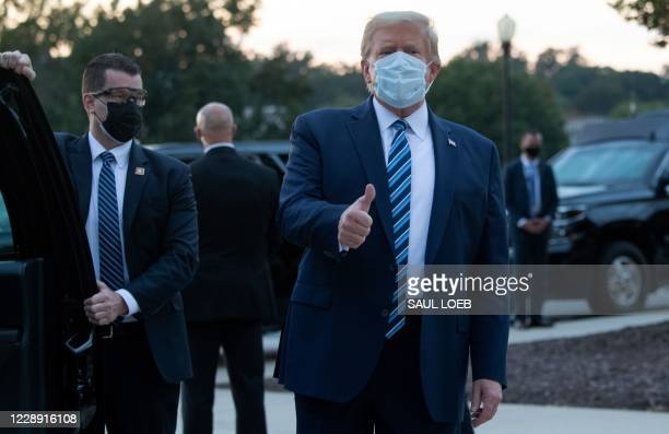 President Donald Trump gives the thumbs-up as he leaves Walter Reed Medical Center in Bethesda, Maryland heading towards Marine One on October 5 to...