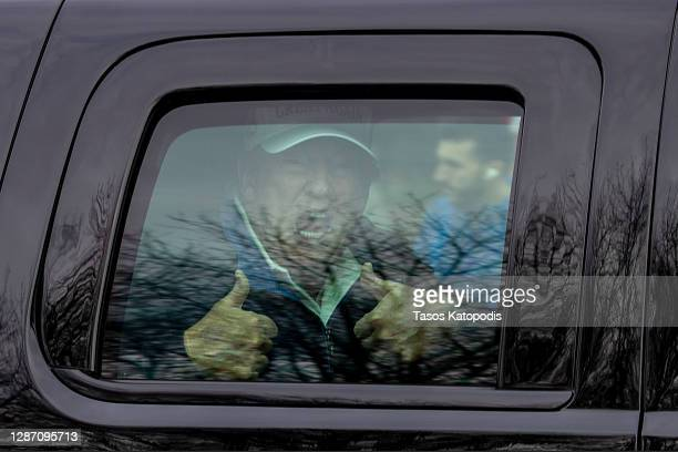 President Donald Trump gives thumbs up to supporters from this motorcade after he golfed at Trump National Golf Club on November 22, 2020 in...